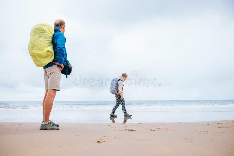 Déplacement avec l'enfant : le père et le fils ont apprécié la plage vide d'océan photo libre de droits
