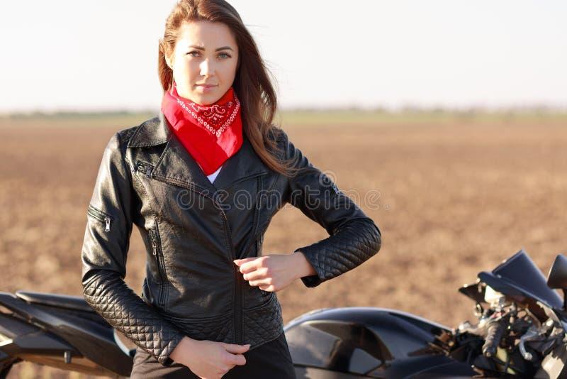 Déplacement sur le vélo Le motocycliste frais beeautiful sérieux ferme la fermeture éclair la veste en cuir noire, a le bandana r photo libre de droits