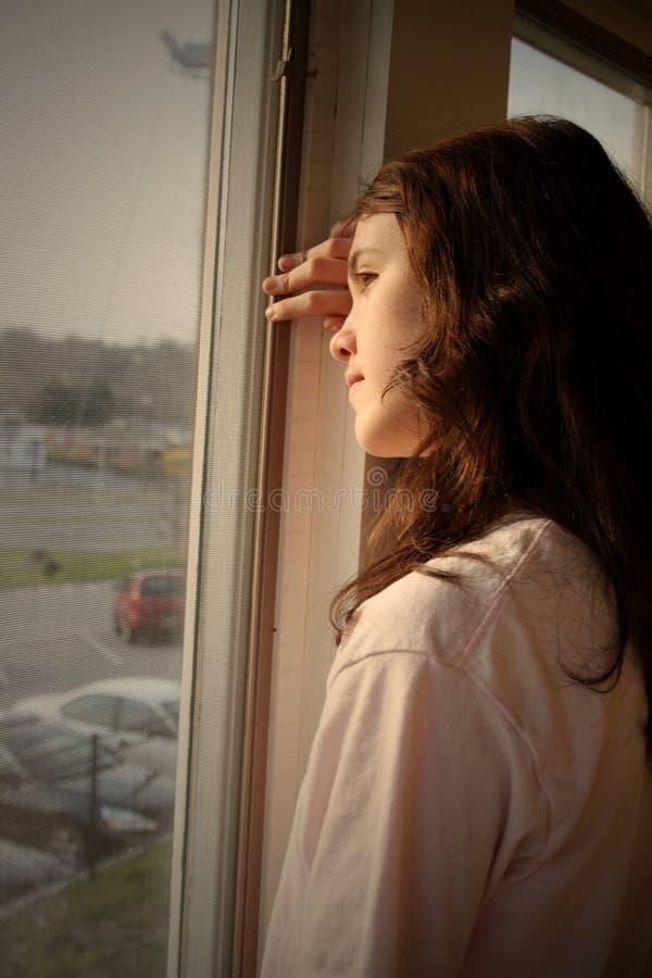 déprimé regardant à l'extérieur l'hublot photos stock