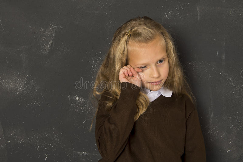 Déprimé triste de belle écolière blonde et fatigué pleurants devant le tableau noir de classe d'école photographie stock
