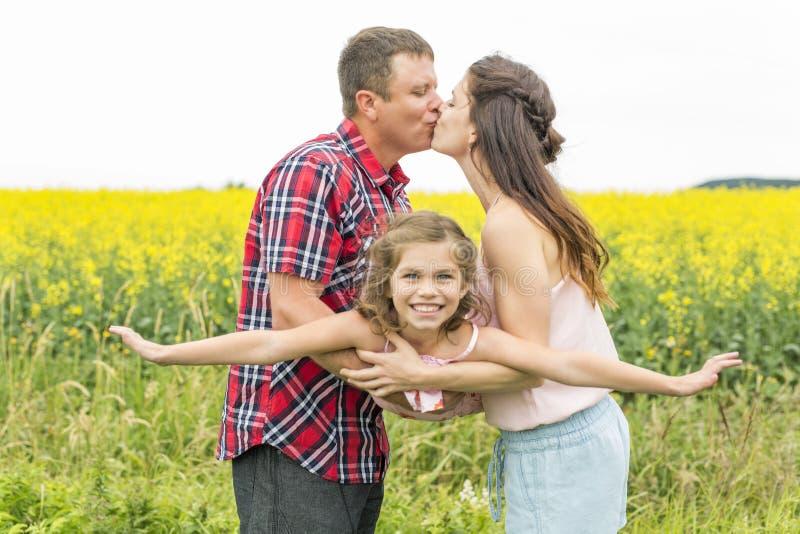 Dérivé heureux d'enfant de ND de couples de famille sur les fleurs jaunes sur la nature en été photo stock