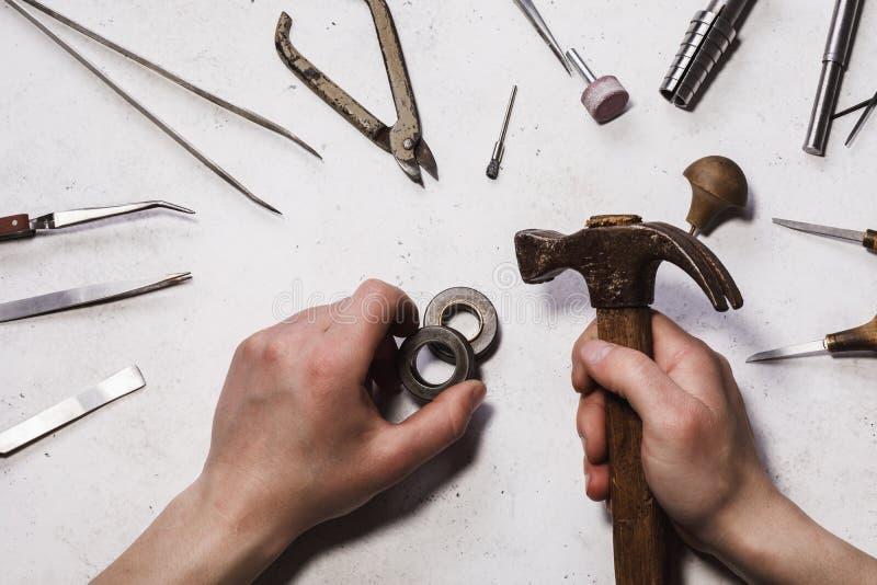 Déroulement des opérations pour réduire l'anneau d'or Le bijoutier dépanne dans l'atelier photo libre de droits