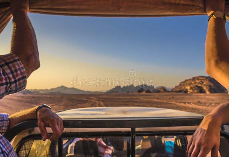 Désert Jordanie de rhum de Wadi on permet à deux touristes de conduire autour dans une jeep par le désert au coucher du soleil, c image libre de droits