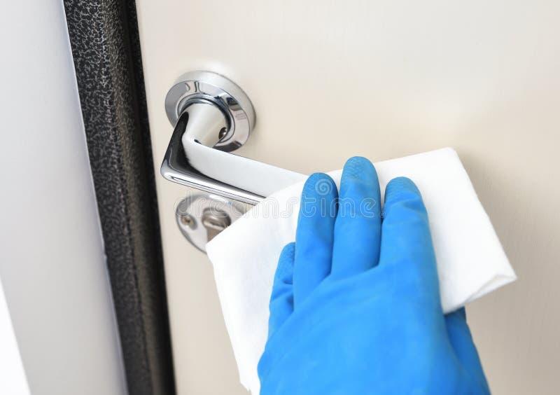 Désinfection dans les lieux publics, lutte contre le virus, coronavirus La main du travailleur efface les poignées de la porte Un photos stock