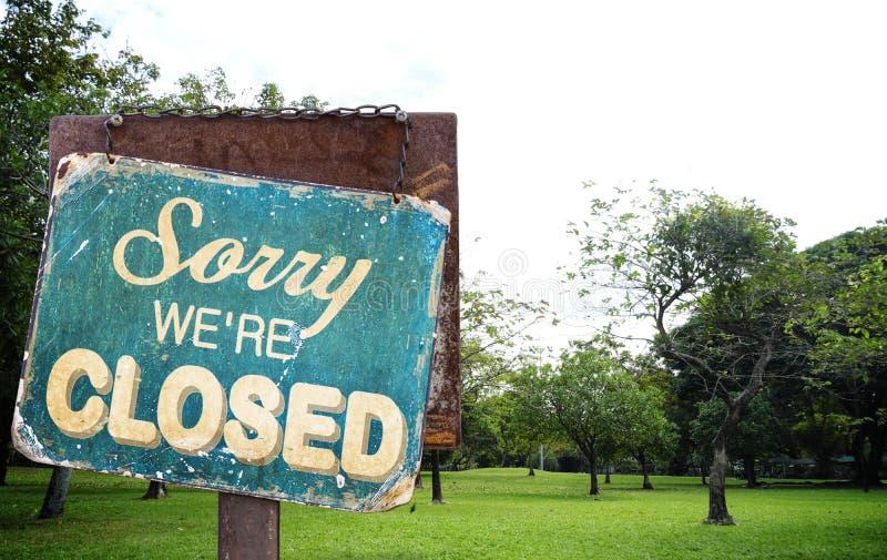 Désolé nous sommes signe fermé accrochant dehors au champ d'herbe verte dedans photos stock