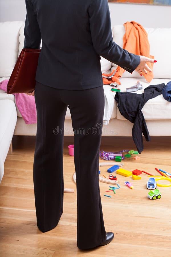 Désordre étonné par femme d'affaires à la maison photographie stock