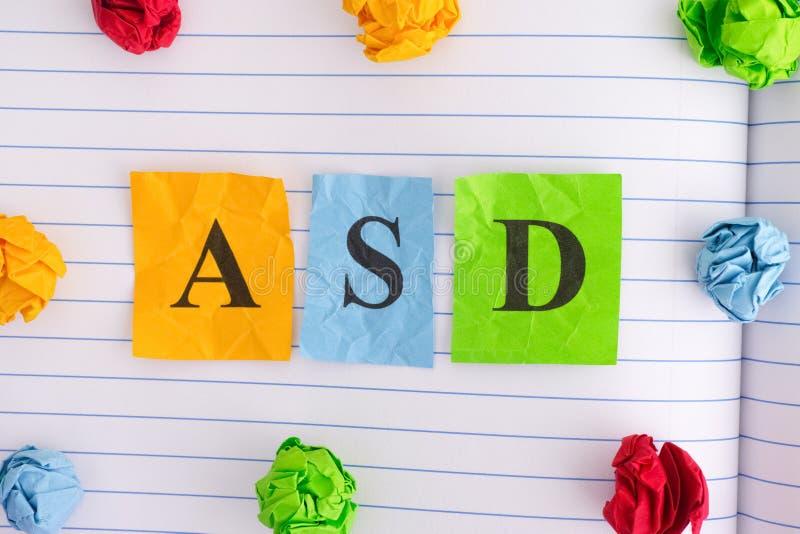 Désordre de spectre d'autisme d'ASD sur la feuille de carnet avec quelques boules de papier chiffonnées colorées autour de elle photo stock
