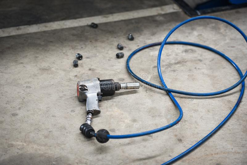 Détachez l'arme à feu pneumatique de main d'outil d'écrou pour l'écrou de roue dans l'atelier mécanique photographie stock libre de droits