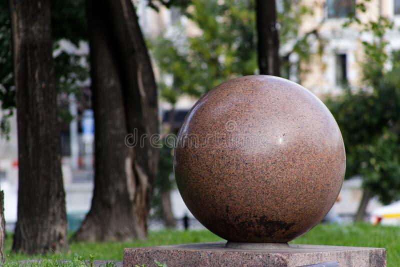 Détail architectural : grande boule en pierre sur un trottoir photographie stock
