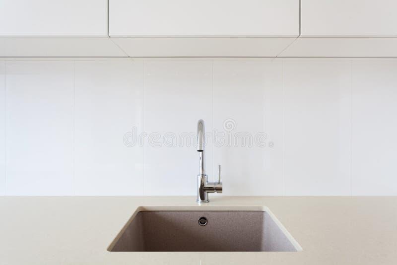 Détail d'un évier de cuisine rectangulaire blanc de concepteur avec le robinet d'eau de chrome image libre de droits