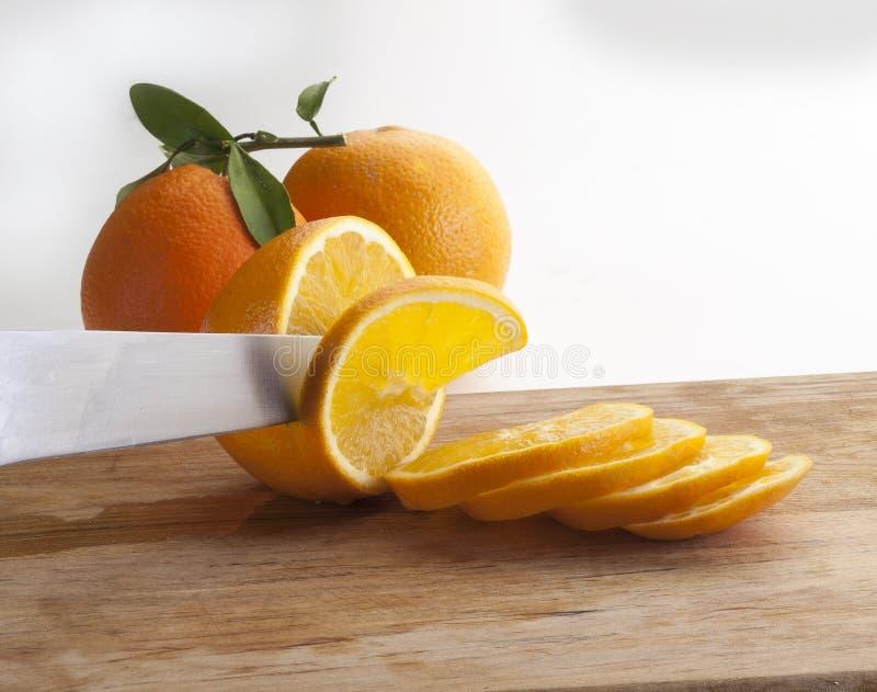 Détail d'un couteau coupant une tranche d'orange sur un conseil en bois images stock