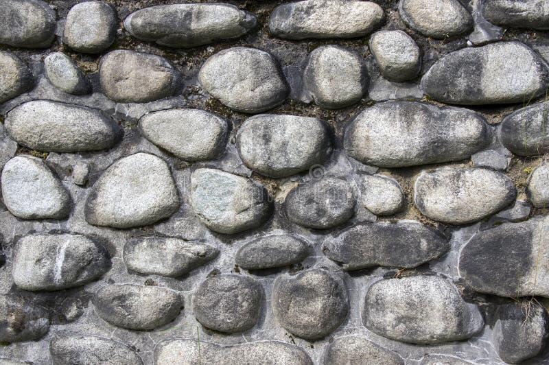 Détail d'un mur fait de pierres de rivière, couleurs foncées en pierre de fond, de mur, de trottoir, grises et brunes photo stock