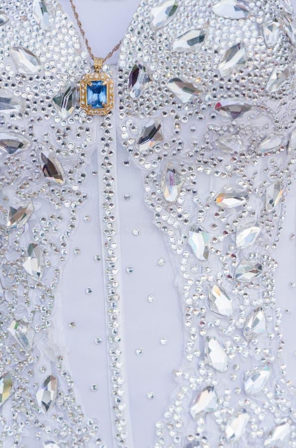 Détail d'une robe de mariage blanche avec des perles et d'un médaillon d'or avec une pierre bleue photographie stock libre de droits