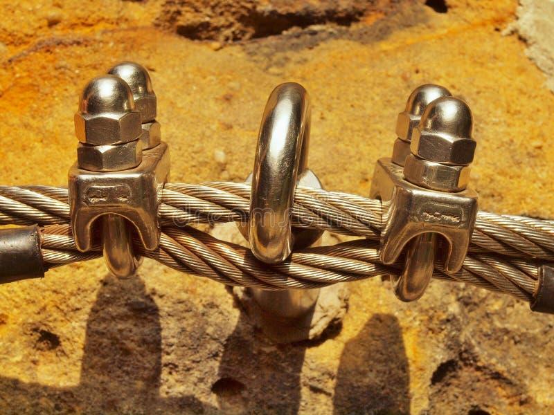 Détail de bride de vis à l'extrémité de la corde d'irone Les grimpeurs repassent la corde tordue fixe dans le bloc par les croche photos libres de droits