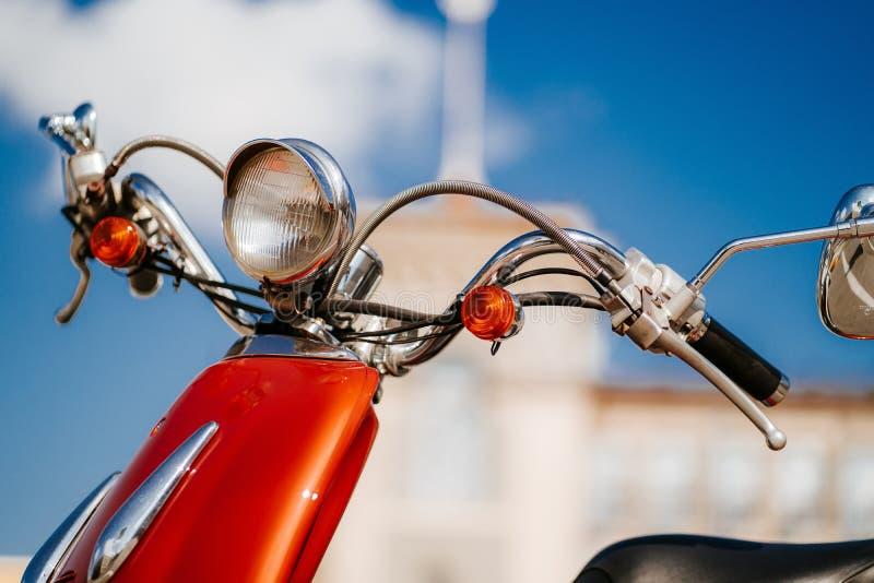 Détail de chrome de plan rapproché et phare de rétro scooter orange de cru sous le ciel bleu et le soleil devant la tour defocuse photo libre de droits