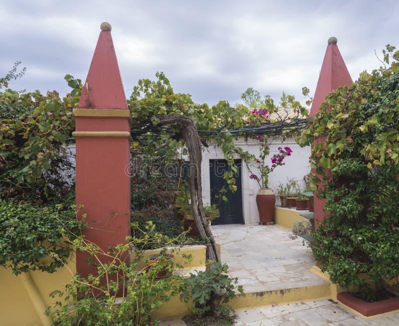 Détail de l'intérieur du monastère orthodoxe de Paleokastritsa, de piliers et de porte rouge avec des pots de fleur et d'axe de v photographie stock libre de droits