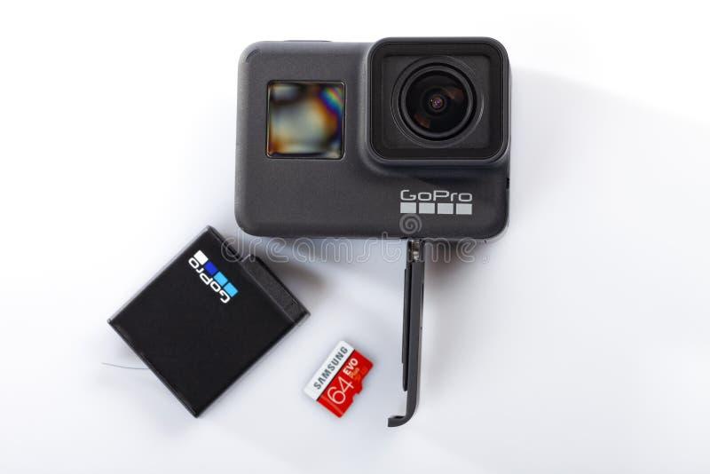 Détail de la manière correcte d'insérer la batterie et la carte de mémoire dans le nouveau noir du héros 7 de GoPro d'isolement image stock