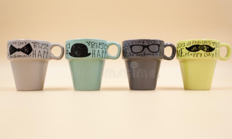 Détail de quatre tasses de café vide avec le message de couleur différente photographie stock libre de droits