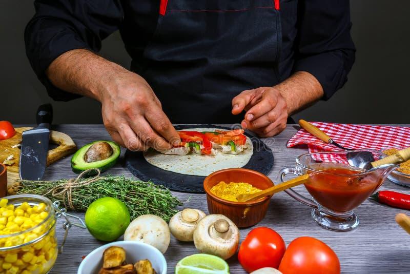 Détail des mains de la tortilla de préparation masculine, mains de burrito de participation de chef Cuisine mexicaine image libre de droits