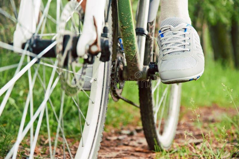 Détail des pieds d'homme de cycliste montant le vélo photographie stock libre de droits