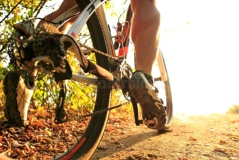 Détail des pieds d'homme de cycliste montant le vélo de montagne sur extérieur image stock