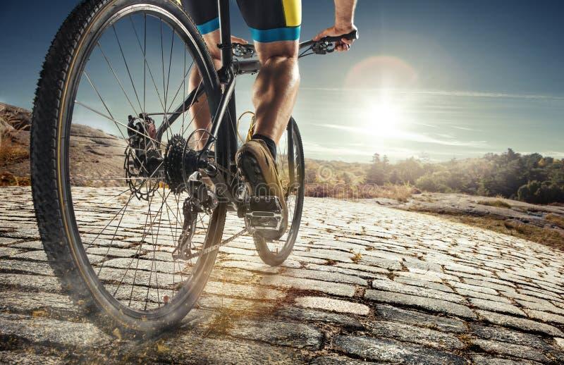Détail des pieds d'homme de cycliste montant le vélo de montagne sur la traînée extérieure sur la route de campagne images libres de droits