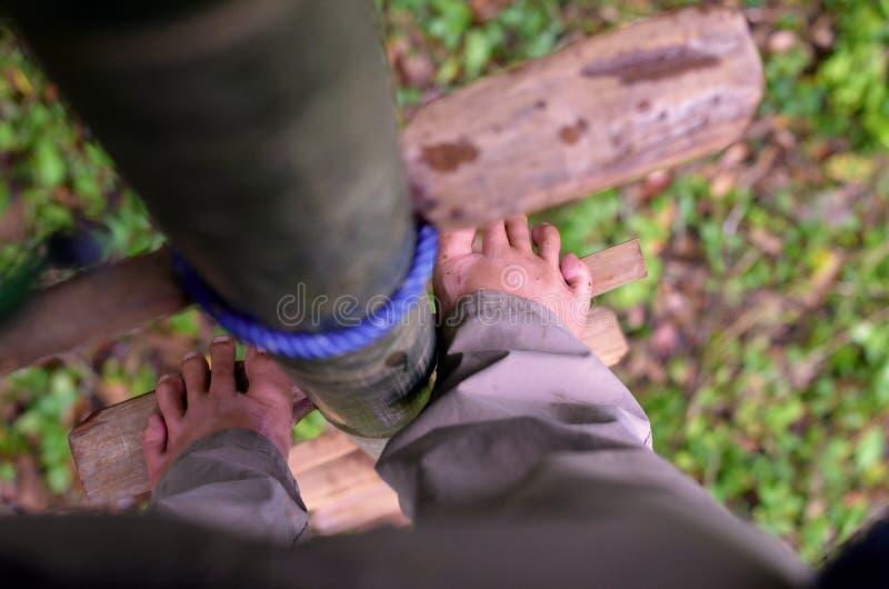 Détail des pieds se tenant sur une échelle en bambou photographie stock libre de droits