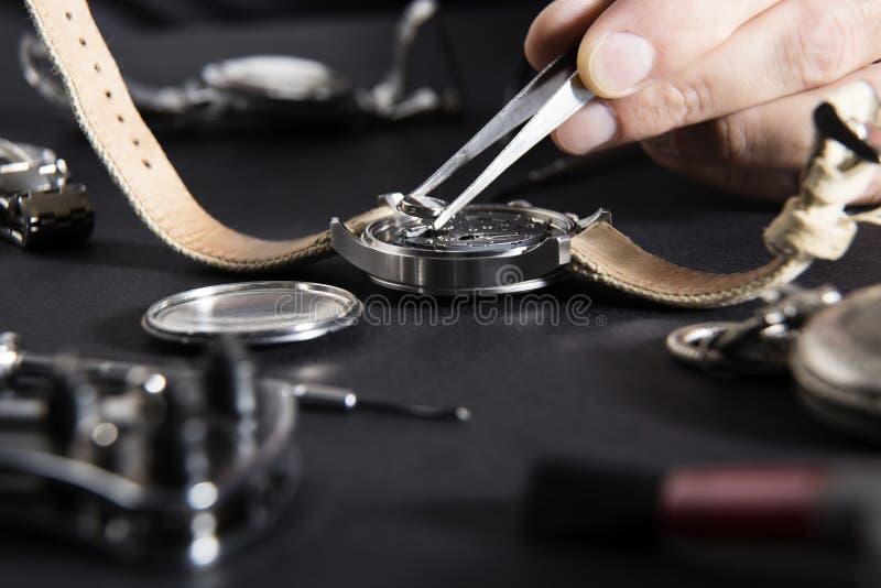 Détail du travail d'un horloger qui remplace une batterie photographie stock libre de droits