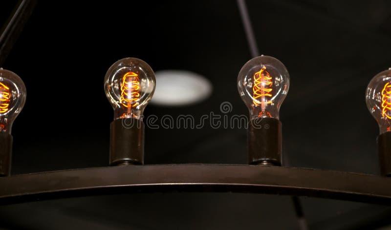 Détail en gros plan des ampoules de vintage dans un métal accrochant l'appareil d'éclairage contre un plafond foncé photo libre de droits