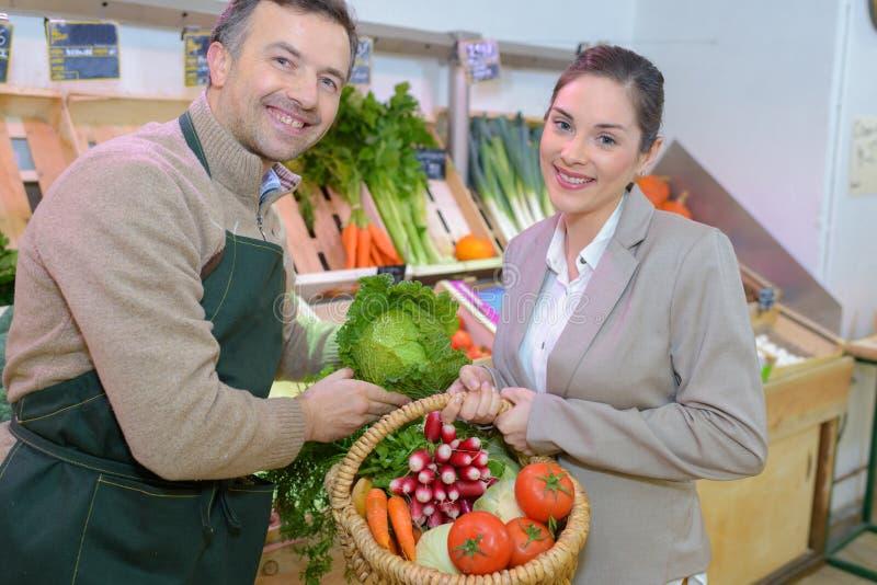 Détaillant et client de portrait tenant les légumes frais de panier image libre de droits