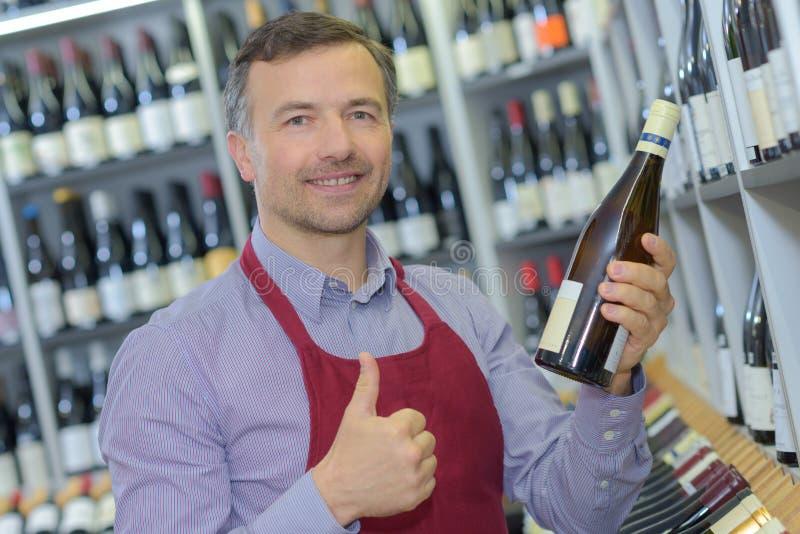 Détaillant tenant le vin de bouteille et faisant le geste positif photos libres de droits