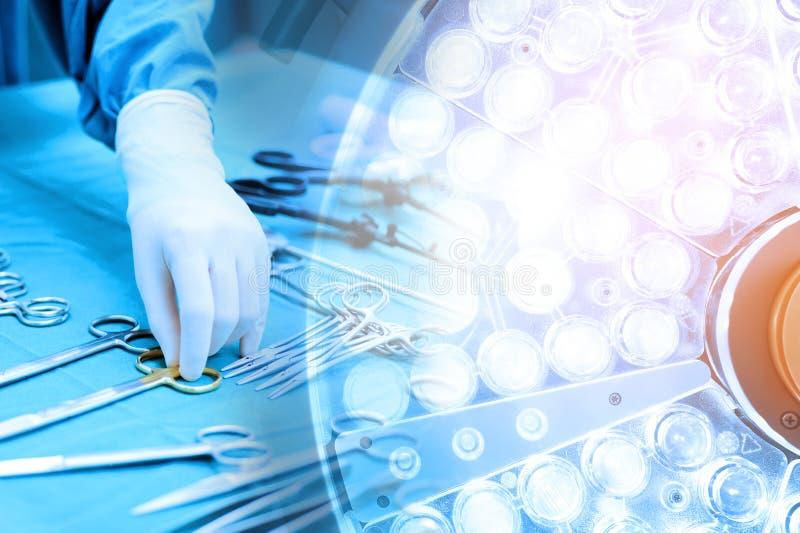 Détaillez le tir des instruments steralized de chirurgie avec une main saisissant un outil et une salle en fonction de lampes chi image stock