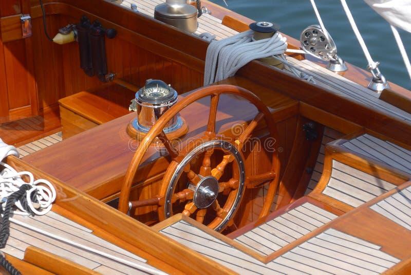 Détaillez les photos d'un yacht de navigation, d'un volant, d'une plate-forme de teck et d'une boussole photos libres de droits