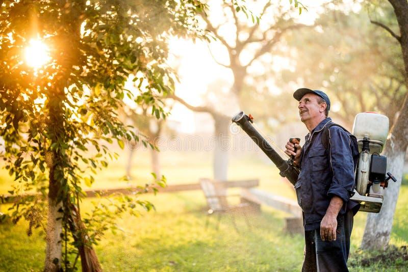 Détails agricoles avec l'agriculteur à l'aide de la machine de pulvérisateur pour le contrôle de pesticide dans le verger de frui photographie stock