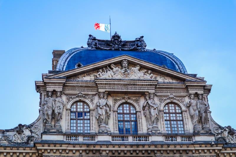 D?tails architecturaux du palais de Louvre avec le drapeau fran?ais Paris, France photos stock