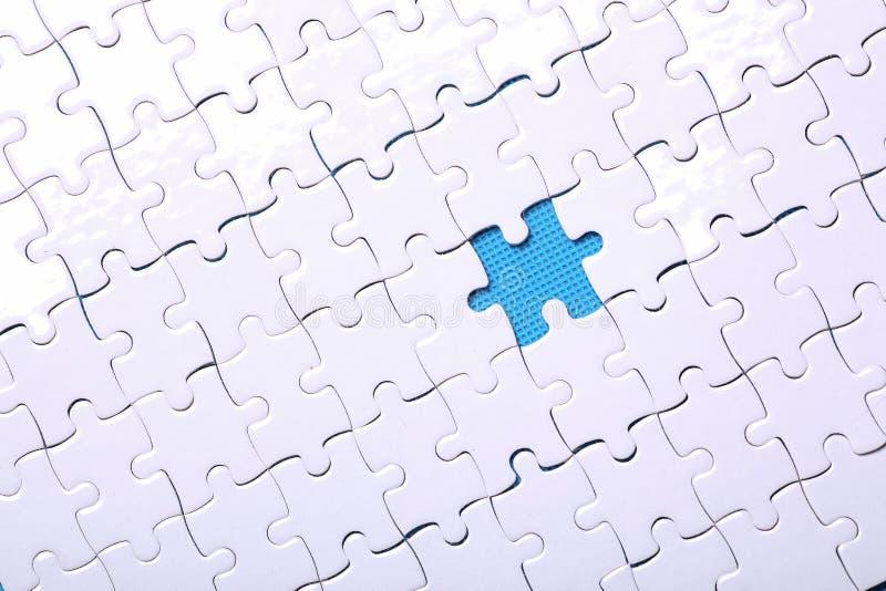 Détails blancs d'un puzzle sur un fond bleu Un puzzle est une unité centrale photographie stock libre de droits