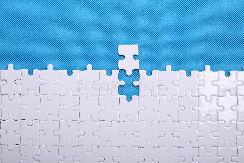Détails blancs d'un puzzle sur un fond bleu Un puzzle est une unité centrale image libre de droits