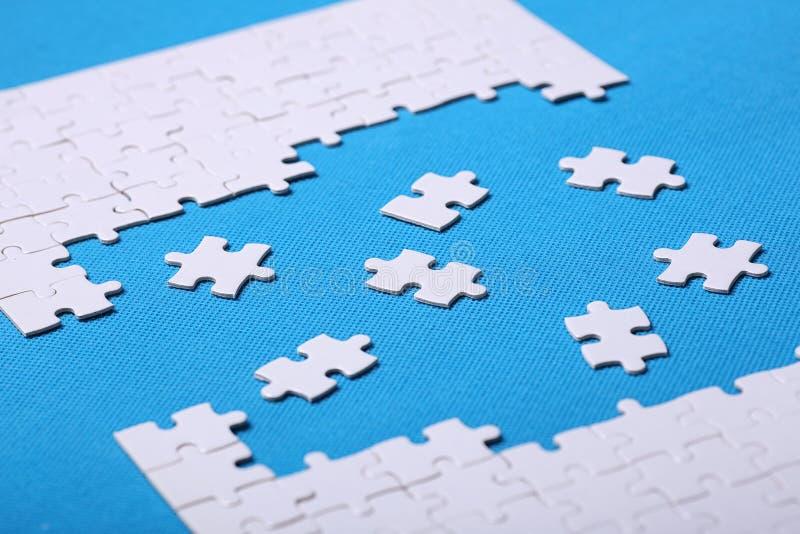 Détails blancs d'un puzzle sur un fond bleu Un puzzle est une unité centrale images stock