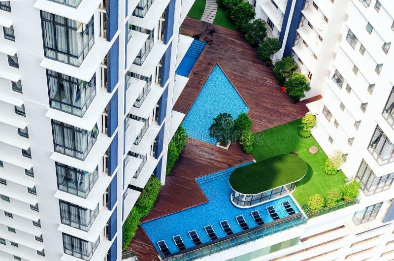 Détails de l'extérieur moderne de bâtiment - patio dans le gratte-ciel avec la piscine, zone de salon, arbres verts photos stock