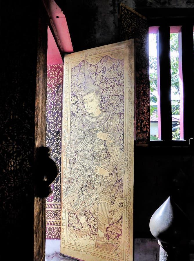 Détails de la peinture traditionnelle thaïlandaise de l'ange dans doré et laqué sur la porte en bois photos libres de droits