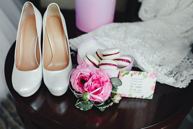 Détails de mariage, décoration Le bouquet des roses roses, les accessoires nuptiales et les macarons se tiennent sur une table en image stock