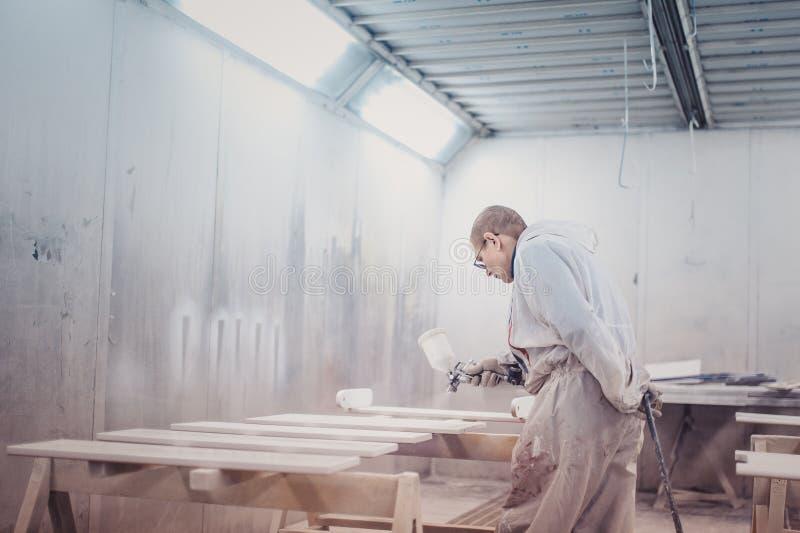 Détails de meubles de peinture d'homme Travailleur à l'aide du pistolet de pulvérisation images stock
