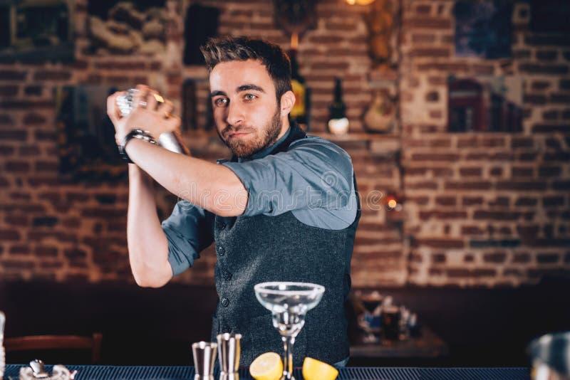Détails de mode de vie avec le barman à l'aide du dispositif trembleur et préparant le cocktail à la barre images stock