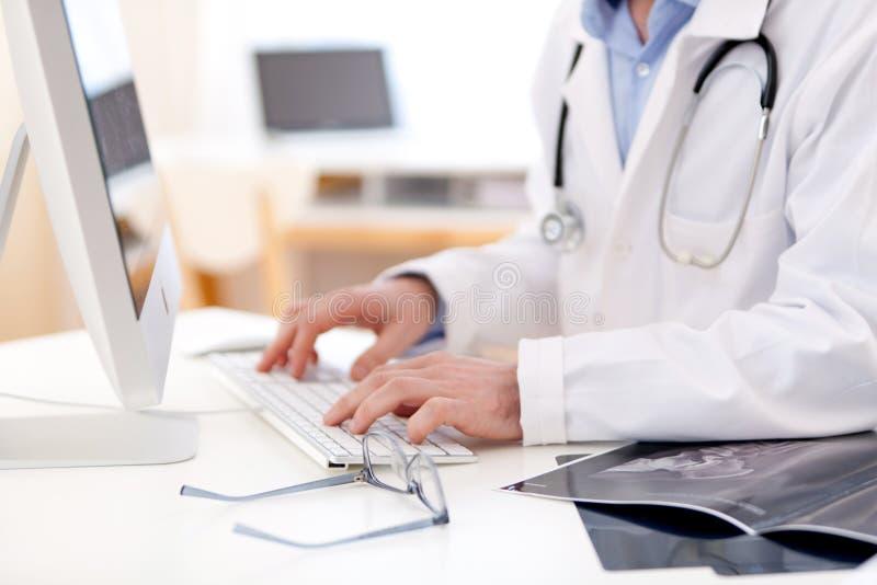 Détails des mains de docteur dactylographiant sur le clavier photo libre de droits