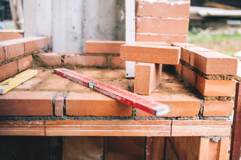 Détails industriels de la maçonnerie, du niveau et des briques sur le chantier de construction photos stock