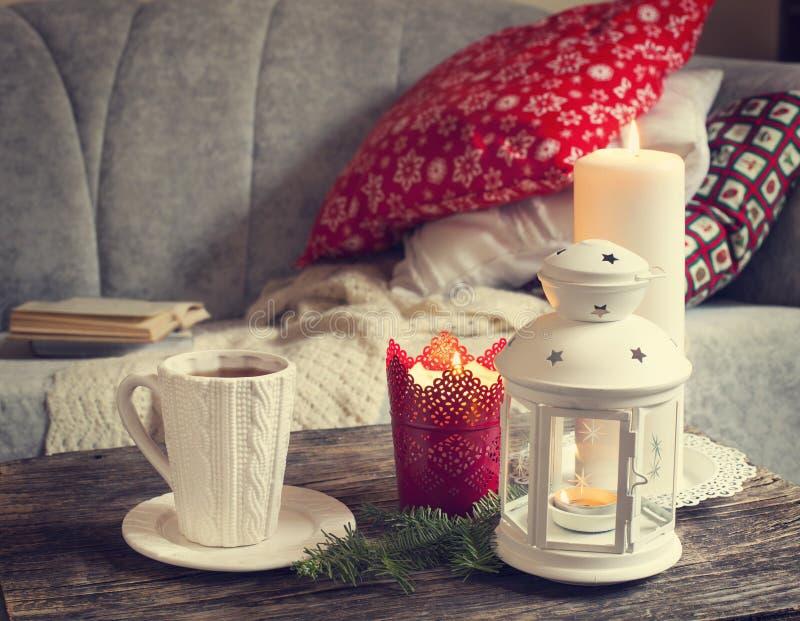 Détails toujours intérieurs de la vie, tasse de thé, bougies près du sofa photographie stock libre de droits