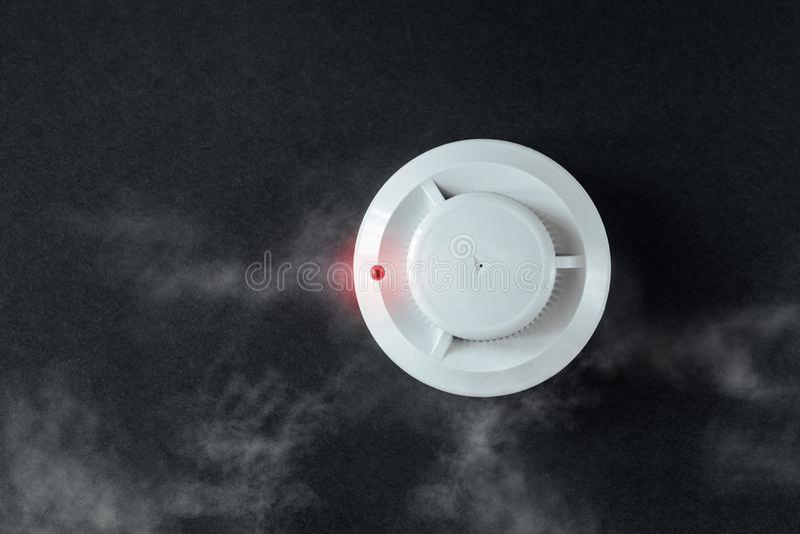 Détecteur d'incendie de détecteur de fumée et sur un fond noir Configuration plate d'alarme d'incendie image libre de droits