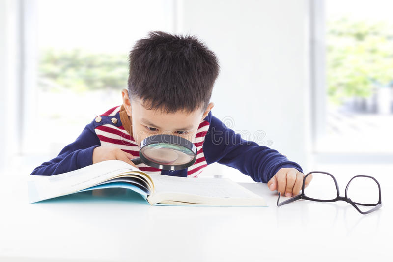 Détective de petit garçon recherchant des indices des livres photos stock
