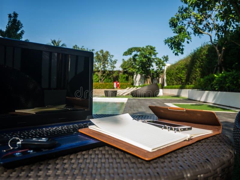 Détendez l'emplacement de travail de temps près de la piscine avec l'ordinateur portable, le carnet et le téléphone photos libres de droits