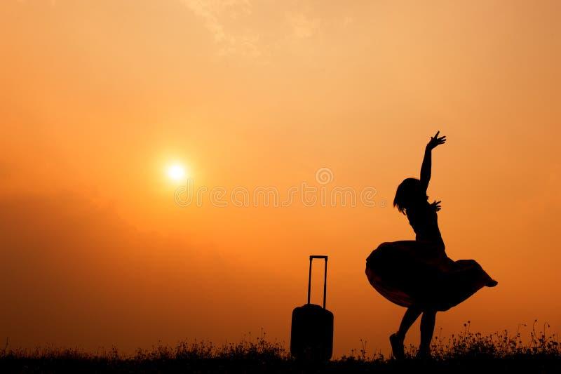 Détendez la femme asiatique avec une valise sur un pré à la silhouette de coucher du soleil Concept de voyage de vacances image stock